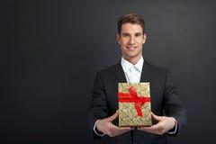 Chiuda su delle mani dell'uomo che tengono il contenitore di regalo Immagini Stock Libere da Diritti