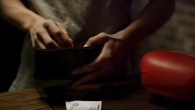 Chiuda su delle mani dell'uomo che tengono un portafoglio di cuoio aperto con alcune monete dentro sopra una vecchia tavola di le fotografia stock