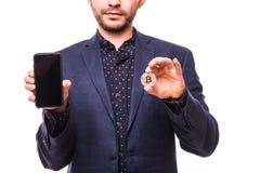 Chiuda su delle mani dell'uomo con il telefono e il bitcoin isolati su fondo bianco immagine stock
