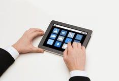 Chiuda su delle mani dell'uomo con le icone di app sul pc della compressa Immagine Stock
