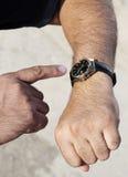 Chiuda su delle mani dell'uomo d'affari che controllano i suoi orologi Fotografie Stock