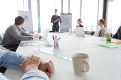 Chiuda su delle mani dell'uomo di affari sulla tavola nel corso della riunione Immagine Stock Libera da Diritti