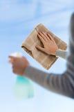 Chiuda su delle mani della donna che puliscono la finestra con il panno Fotografie Stock