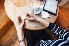 Chiuda su delle mani della donna che scrivono gli stickies delle note dalla matita di legno Giovane bella donna che scrive il suo Fotografie Stock