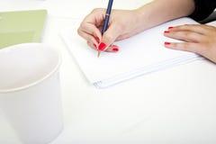 Chiuda su delle mani della donna che scrivono sulla carta. fotografia stock libera da diritti