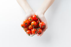 Chiuda su delle mani della donna che tengono i pomodori ciliegia Fotografie Stock Libere da Diritti