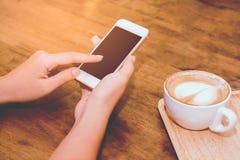 Chiuda su delle mani della donna che tengono il contatto del telefono cellulare con lo spazio in bianco della copia per il vostro immagine stock
