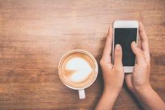 Chiuda su delle mani della donna che tengono il contatto del telefono cellulare con lo spazio in bianco della copia per il vostro immagini stock