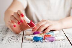 Chiuda su delle mani della donna con gli smalti dei colori differenti Fotografie Stock Libere da Diritti