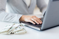 Chiuda su delle mani della donna con il computer portatile ed i soldi Fotografie Stock Libere da Diritti