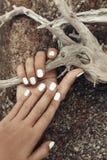 Chiuda su delle mani della donna con il manicure bianco Immagine Stock