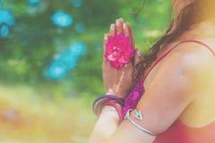 Chiuda su delle mani della donna di yoga nel gesto del namaste con il fiore rosa Immagini Stock