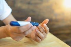 Chiuda su delle mani della donna facendo uso della lancetta sul dito per controllare il livello della glicemia dal metro del gluc fotografia stock