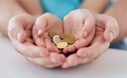 Chiuda su delle mani della famiglia che tengono le euro monete dei soldi Fotografie Stock Libere da Diritti