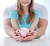 Chiuda su delle mani della famiglia con il porcellino salvadanaio Immagine Stock Libera da Diritti