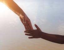 Chiuda su delle mani della madre o della sorella più anziana e di un bambino al tramonto con lo spazio della copia Immagine Stock Libera da Diritti