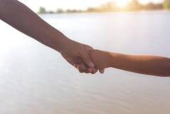 Chiuda su delle mani della madre o della sorella più anziana e di un bambino al tramonto con lo spazio della copia Fotografie Stock Libere da Diritti