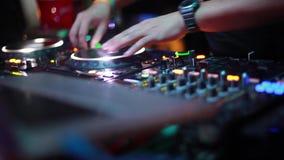 Chiuda su delle mani della miscelazione e dello scratch di musica dei giochi del DJ sull'attrezzatura di musica della piattaforma stock footage
