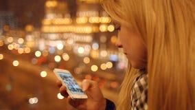 Chiuda su delle mani della ragazza che scrivono gli sms a macchina che fanno scorrere il telefono delle immagini 4K 30fps ProRes video d archivio