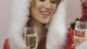Chiuda su delle mani della ragazza che tostano con i bocals di champagne e di bere lentamente stock footage