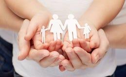 Chiuda su delle mani della ragazza e della donna con la famiglia di carta Immagine Stock
