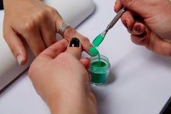 Chiuda su delle mani delle donne con i chiodi dipinti e dei campioni minerali coordinati degli ombretti nei colori festivi sul ne Fotografie Stock