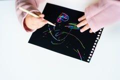 Chiuda su delle mani di piccolo bambino che attinge la carta magica della pittura del graffio con il bastone del disegno fotografia stock libera da diritti