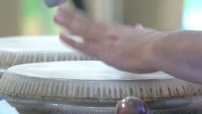Chiuda su delle mani di un uomo che gioca una percussione del tamburo video d archivio