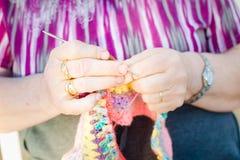 Chiuda su delle mani di una signora anziana che tricotta sui ferri da maglia, facendo uso della lana variopinta immagine stock
