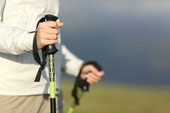 Chiuda su delle mani di una viandante che camminano con i pali fotografie stock libere da diritti