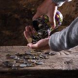Chiuda su delle mani e del mucchio dell'uomo anziano caucasico di vecchie monete Immagini Stock Libere da Diritti