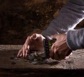 Chiuda su delle mani e del mucchio dell'uomo anziano caucasico di vecchie monete Fotografia Stock