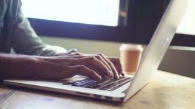 Chiuda su delle mani facendo uso del computer portatile in caffè archivi video