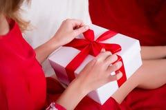 Chiuda su delle mani femminili che aprono il regalo Fotografia Stock