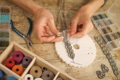 Chiuda su delle mani femminili che fanno un braccialetto di macramè con il kumihimo su una tavola di legno con gli strumenti, le  immagini stock