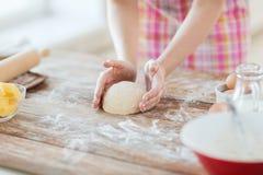 Chiuda su delle mani femminili che impastano la pasta a casa Immagini Stock Libere da Diritti