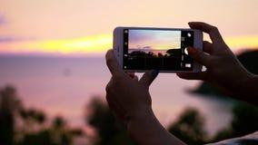 Chiuda su delle mani femminili che prendono le immagini del tramonto scenico del mare con il telefono Movimento lento 1920x1080 stock footage