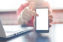 Chiuda su delle mani femminili che tengono lo smartphone in bianco, indicando un dito allo schermo dello spazio della copia per l Fotografia Stock