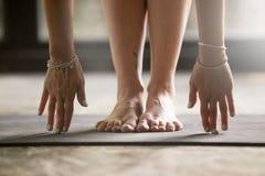 Chiuda su delle mani femminili che toccano la stuoia di yoga immagini stock