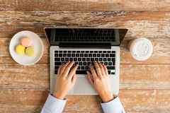 Chiuda su delle mani femminili con il computer portatile ed il caffè Immagini Stock