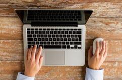 Chiuda su delle mani femminili con il computer portatile ed il topo Fotografie Stock Libere da Diritti