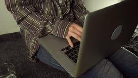 Chiuda su delle mani femminili facendo uso del computer portatile che si siede sul pavimento a casa archivi video