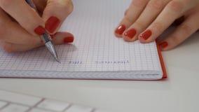 Chiuda su delle mani femminili scrivono la nota in taccuino accanto alla tastiera di computer bianca archivi video