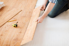 Chiuda su delle mani maschii che intalling la pavimentazione di legno Immagini Stock