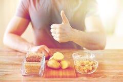 Chiuda su delle mani maschii con l'alimento del carboidrato immagini stock