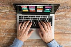 Chiuda su delle mani maschii con la battitura a macchina del computer portatile Immagini Stock