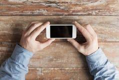 Chiuda su delle mani maschii con lo smartphone sulla tavola Fotografie Stock Libere da Diritti