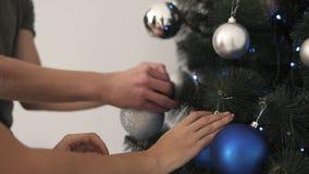 Chiuda su delle mani maschii e femminili, coppie che decorano l'albero di abete a casa con le palle colorate blu e d'argento oper archivi video