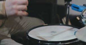 Chiuda su delle mani maschii facendo uso delle bacchette che giocano i tamburi archivi video