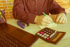 Chiuda su delle mani maschii sulla sua tastiera del ` s del calcolatore La seconda mano dentro sul touchpad Concetto del lavoro d Fotografia Stock